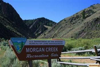 The sign at the entrance to Morgan Creek Recreation Site and view of nearby mountains.