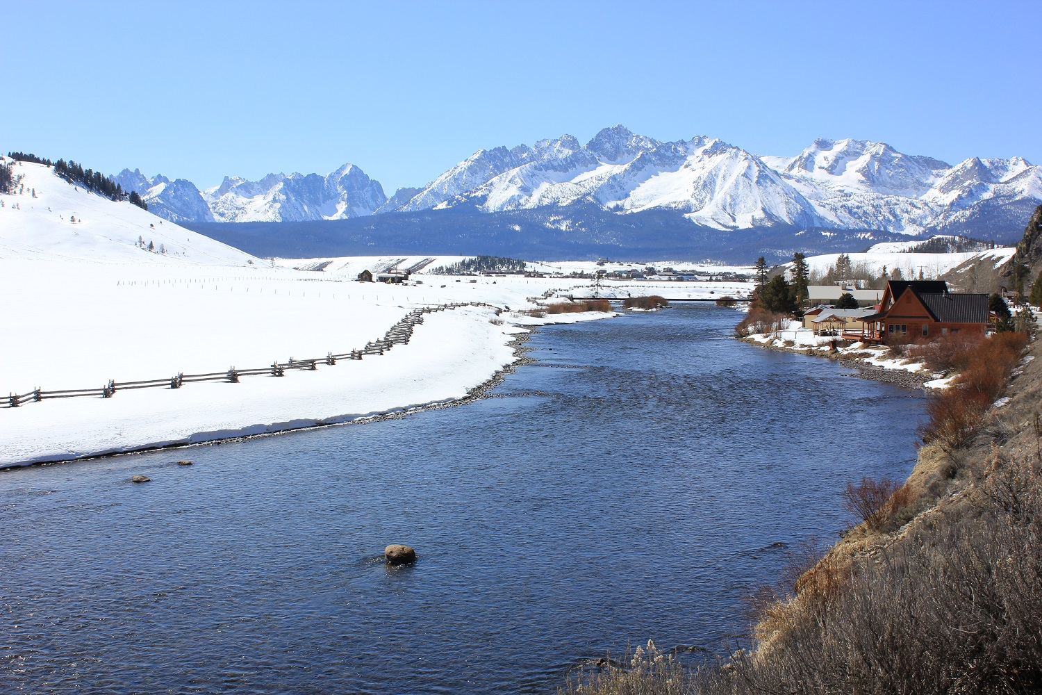 The Salmon River in the winter with the Sawtooth Mountains and Stanley, Idaho in the background.